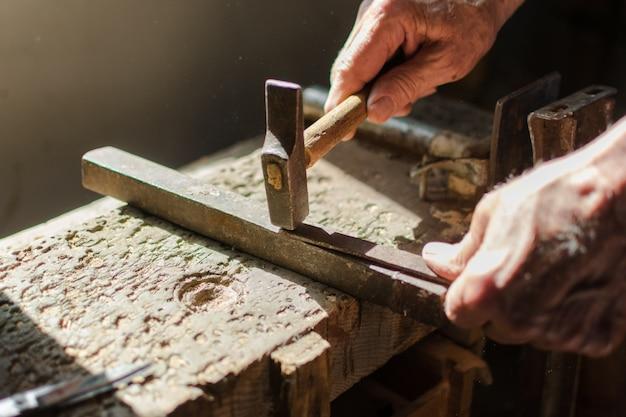 Handen van een bejaarde die aan het ijzer met de hamer werkt.