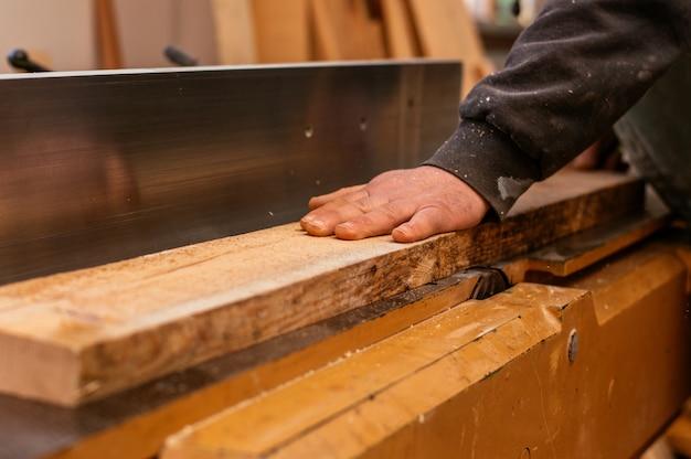 Handen van een bekwame timmerman tijdens het werken