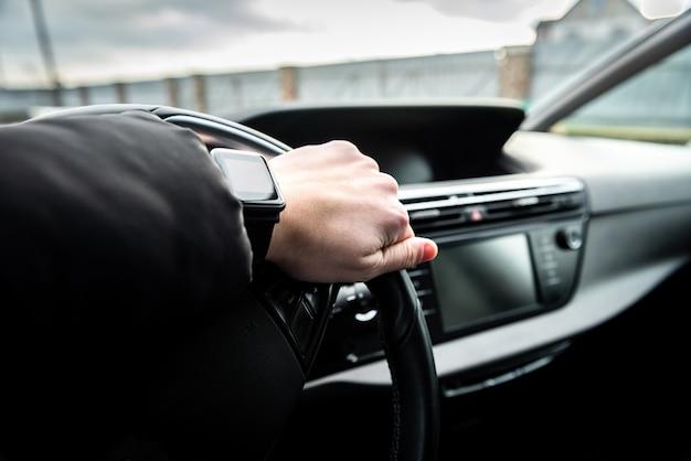 Handen van een bestuurder op het stuur van een auto.