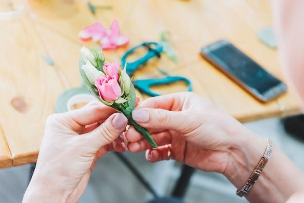 Handen van een bloemist die boutonnières maakt