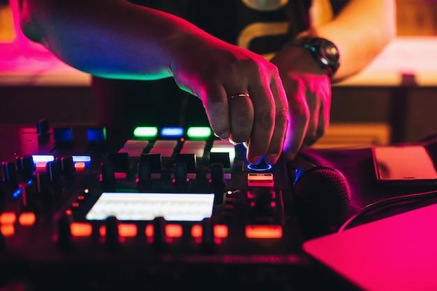 Handen van een dj die bij een professionele mixer in nachtclub speelt