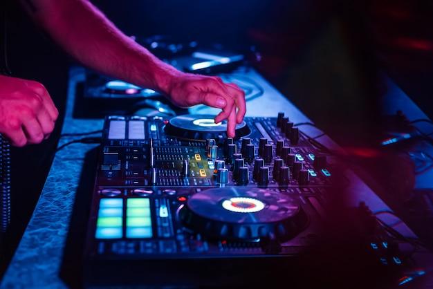 Handen van een dj die muziek mengt op een professionele controller in een cabine