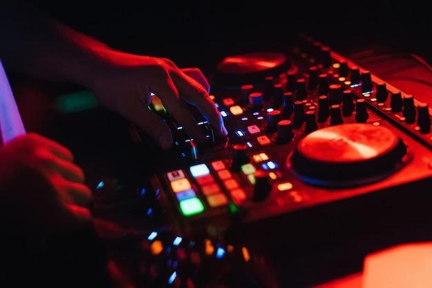 Handen van een dj in een cabine die op de mixer speelt