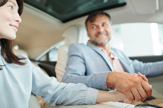 Handen van een eigentijds aanhankelijk stel van middelbare leeftijd dat op de achterbank van een nieuwe auto zit en elkaar aankijkt tijdens een proefrit