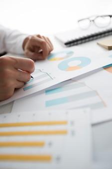 Handen van een financieel analist die met een statistische grafiek werkt.