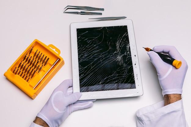 Handen van een gehandschoende technicus die een tablet met een gebroken glas herstelt