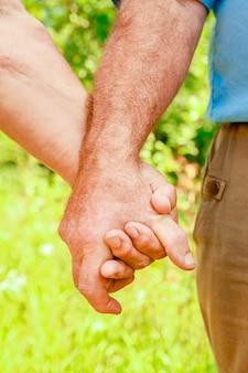 Handen van een gelukkig stel van middelbare leeftijd op de natuur