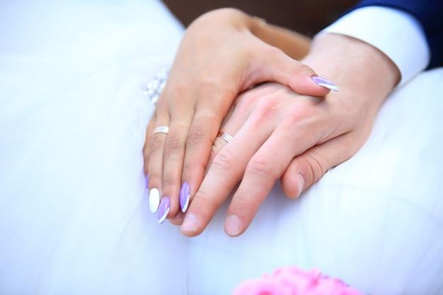 Handen van een getrouwd stel met trouwringen
