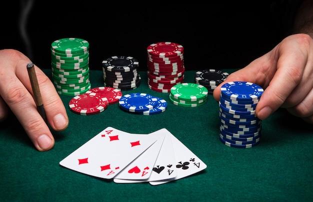 Handen van een gokker close-up en chips op groene tafel in een pokerclub