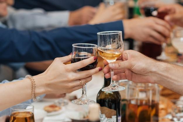 Handen van een groep vrienden die glazen wijn en het roosteren rammelen