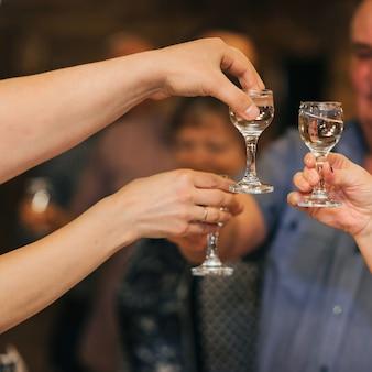 Handen van een groep vrienden die glazen wodka rammelen en de vakantie vieren