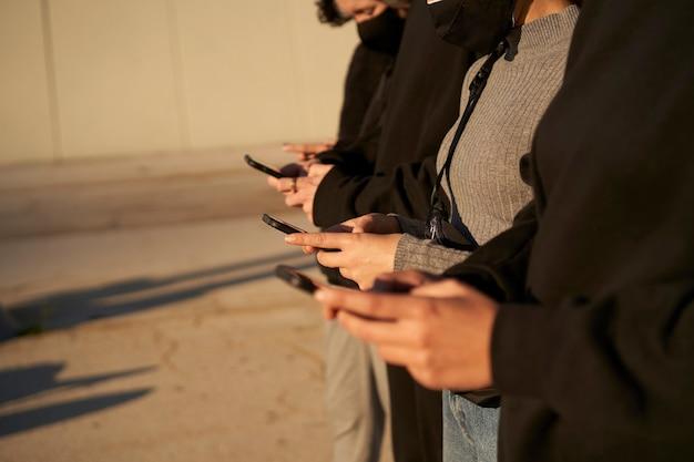 Handen van een groep vrienden met behulp van smartphones