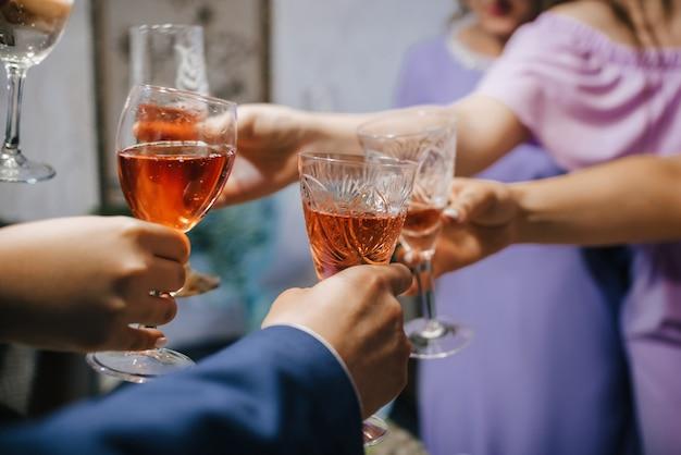 Handen van een groep vrienden rammelende glazen alcoholische drank en roosteren en feliciteren