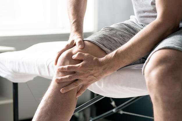 Handen van een hedendaagse volwassen man die zijn rechterknie masseert terwijl hij op tafel zit voor fysiotherapeutische procedures in klinieken of medische kantoren