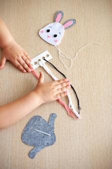 Handen van een jong meisje close-up, ze naait een macramé speelgoed van draad.