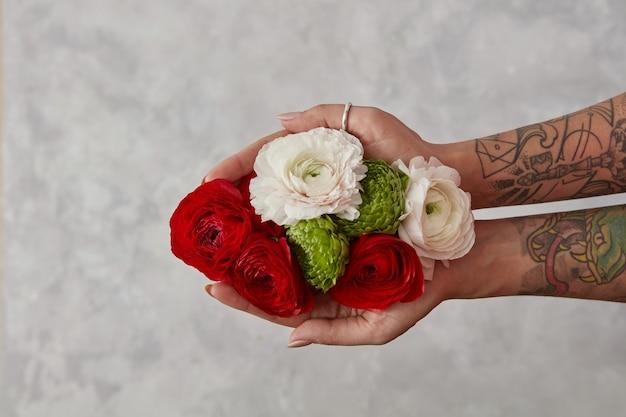 Handen van een jong meisje met een tatoeage, met een boeket bloemen op een grijze achtergrond, concept van een wenskaart bovenaanzicht