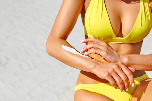 Handen van een jong meisje sunblock toe te passen zittend op een strand in de zomer