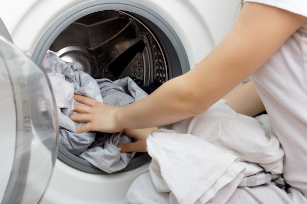 Handen van een jong meisje zetten kleren in de trommel van de wasmachine