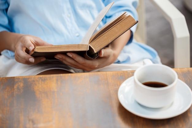 Handen van een jong meisje zitten aan de tafel met boek en koffiekopje.