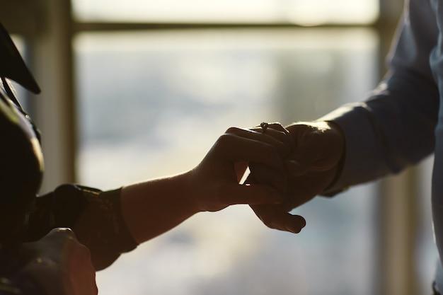 Handen van een jong stel met een ring. close-up van de man die diamanten ring geeft aan de vrouw