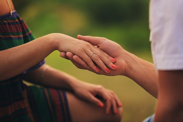 Handen van een jong stel met een ring