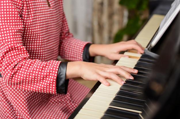 Handen van een jong vrouwelijk kind die klassieke muziek thuis uitvoeren