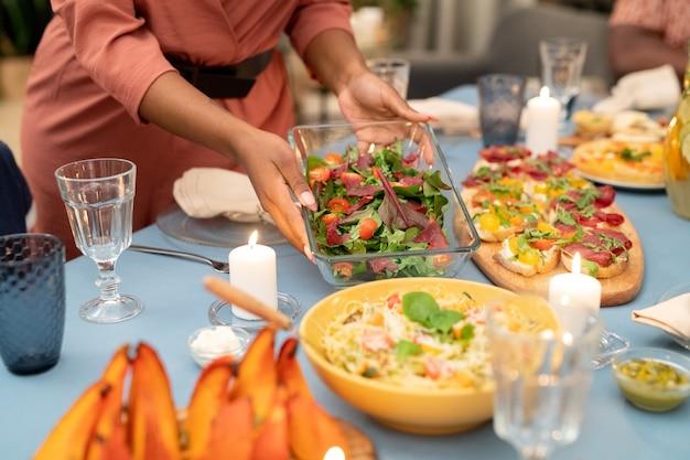 Handen van een jonge afrikaanse vrouw die een glazen kom met verse groentesalade op een feestelijke tafel zet met zelfgemaakte sandwiches en pasta