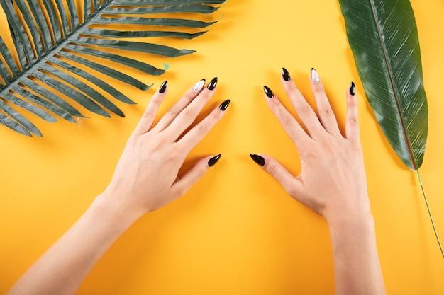 Handen van een jonge vrouw aan tafel met bladeren op een oranje achtergrond