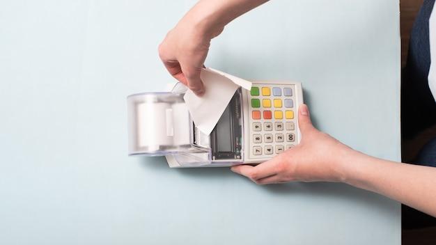 Handen van een jonge vrouw die een cheque uit de kassa scheurt na aankoop van een product