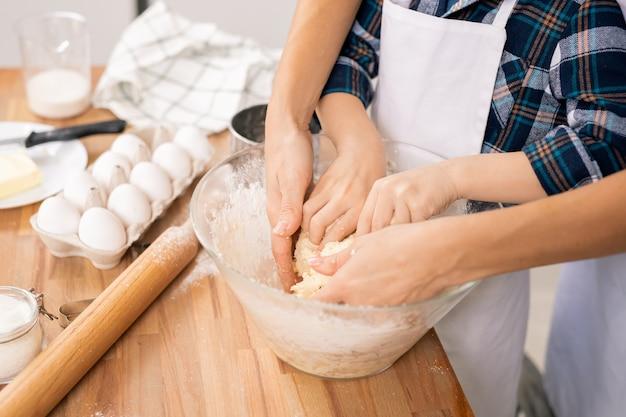 Handen van een jonge vrouw en haar zoontje die zelfgemaakt deeg in een kom kneden terwijl ze allebei bij de tafel in de keuken staan