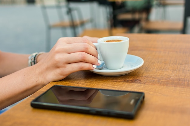 Handen van een jonge vrouw houden een kopje koffie op een terras van een pub