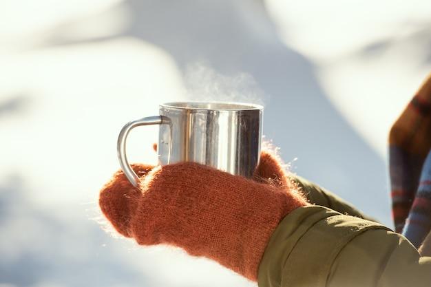 Handen van een jonge vrouw in warme winterkleding die een metalen mok met hete thee vasthoudt terwijl ze voor de camera staat tegen schaduwen op sneeuw