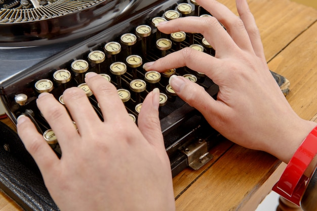 Handen van een jonge vrouw met een oude typemachine