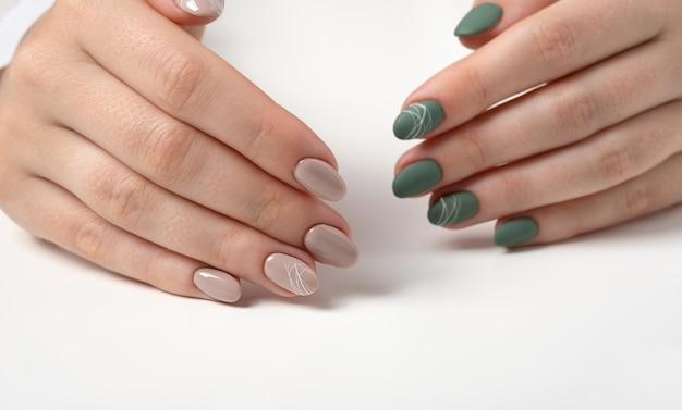 Handen van een jonge vrouw met groene olijf matte nagels en beige glanzende nagels op een lichtgrijze achtergrond. nagels van verschillende kleuren. manicure, schoonheidssalon. ruimte voor tekst of logo kopiëren. abstract