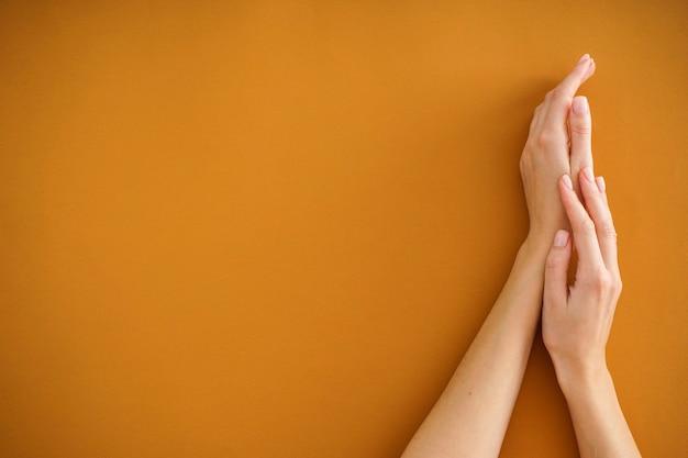 Handen van een jonge vrouw met mooie manicure op een beige achtergrond. vrouwelijke manicure. plat leggen, plaats voor tekst.