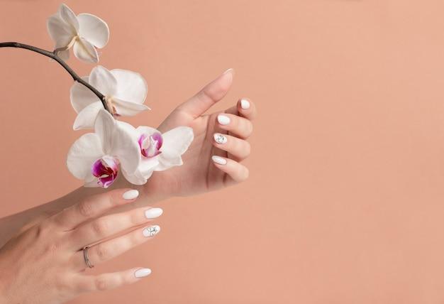 Handen van een jonge vrouw met witte lange nagels op een beige achtergrond met orchideebloemen.