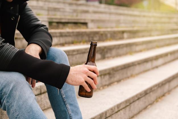 Handen van een jonge vrouw of tiener die een flesje bier op straat houdt. concept tienerprobleem en illegale feesten met een verbod op alcohol.