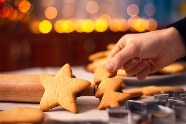 Handen van een jongen die kerstkoekjes neemt
