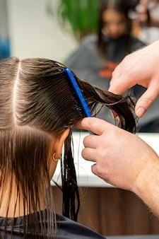 Handen van een kapper die het haar van een jonge vrouw kamt