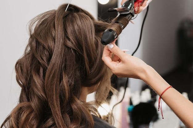 Handen van een kapper met een krultang die een kapsel maakt voor een krullend meisje in een professionele schoonheidssalon