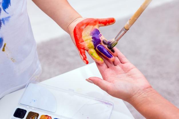 Handen van een kind beschilderd met felle kleuren.