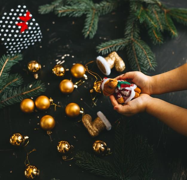 Handen van een kind dat een stuk speelgoed van kerstmis houdt
