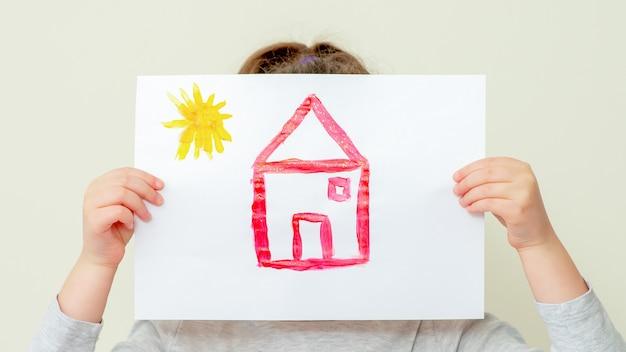 Handen van een kind met een foto van een huis dat haar gezicht bedekt op een lichte achtergrond.
