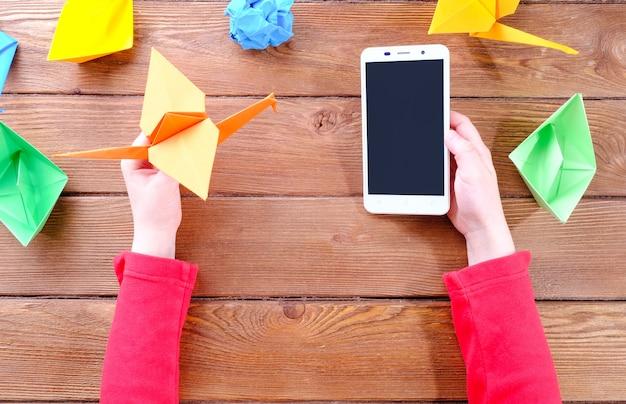 Handen van een kind met een telefoon en origami van gekleurd papier op een houten tafel