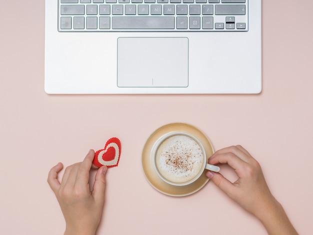 Handen van een kind met koffie en een hartcijfer dichtbij laptop