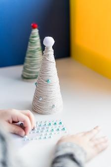 Handen van een klein meisje maken draad kerstboom. handgemaakte gebreide kerstcadeau. kerstboom