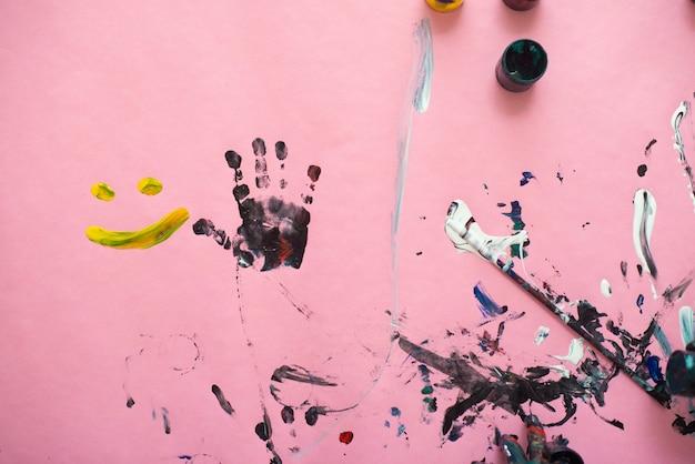 Handen van een kleine jongen die met waterverf op roze document blad schildert. kleine jongen met een penseel en verf.
