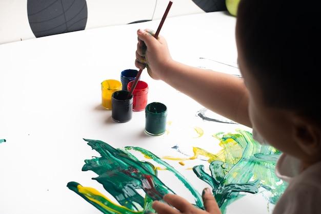 Handen van een kleine jongen die met waterverf op witboekblad schildert.