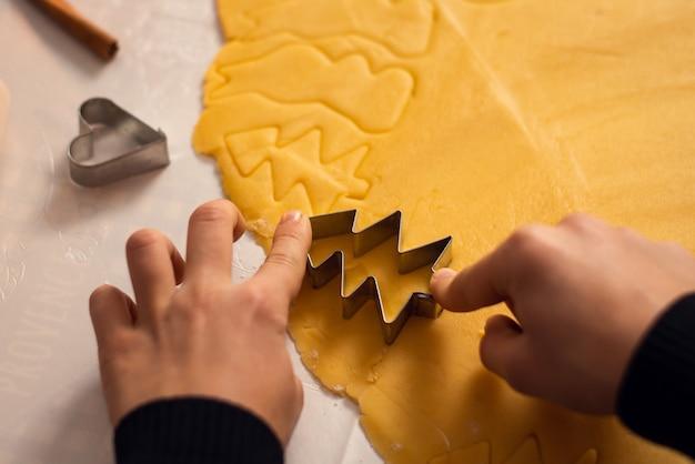 Handen van een kleine jongen die zijn moeder helpt bij het maken van koekjes in de vorm van de kerstboom met behulp van een vorm voor deeg