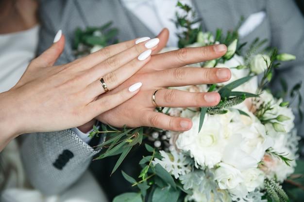Handen van een knappe man en een vrouw op de dag van hun huwelijk